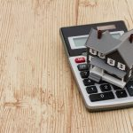 A gray house and calculator on wood background with copy space for your message