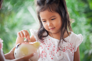 Image of a young girl learning savings habits by using a piggy bank