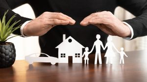 Image of hands over a family and their assets, representing an insurance policy