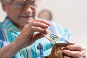 Image of a senior woman saving a banknote in her purse