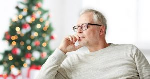 Image of a senior man looking worried in front of a Christmas tree
