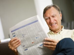 Image of a happy senior reading the stock listings for the energy sector