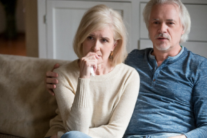 Image of a concerned senior couple watching the news