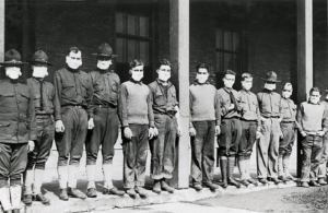 Image of a line of army medics wearing masks to prevent infection with the Spanish Flu