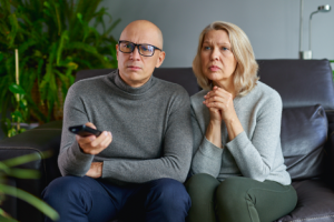 Image of a concerned middle-aged couple watching the news in their living room