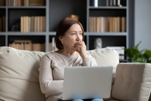 Image of a pensive senior woman thinking while holding her laptop