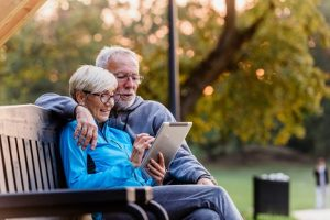 Image of a senior couple out in nature looking at a tablet