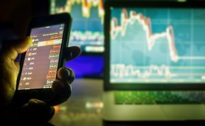 Image of a hand holding a phone used for day trading while a computer shows stock charts in the background