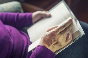 Image of a senior woman reading a book
